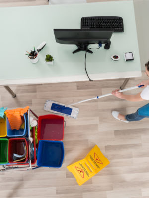 Young female janitor mopping wooden floor with caution sign for end of tenancy